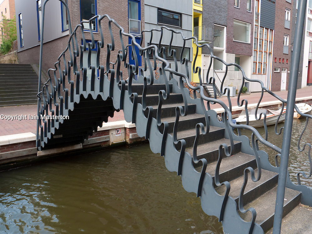 Modern ornate steel footbridge crossing canal in new Java Island housing development in Amsterdam The Netherlands
