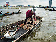 14 OCTOBER 2015 - BANGKOK, THAILAND:  A spotter spools out air hose for the diver he works with, who is at the bottom of the Chao Phraya River in Bangkok. Divers work in two man teams on small boats in the Chao Phraya River. One person stays in the boat while the diver scours the river bottom for anything that can be salvaged and resold. The divers usually work close to shore because the center of the river is a busy commercial waterway with passenger boats and commercial freight barges passing up and down the river all day long. The Chao Phraya is a dangerous river to dive in. It's deep, has large tidal fluctuations, is fast flowing and badly polluted. The divers make money only when they sell something.   PHOTO BY JACK KURTZ