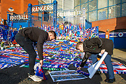 Two fans add their tribute on impromptu memorial on the gates of Ibrox Stadium, Glasgow, Scotland to Fernando Ricksen, the former Rangers player, who sadly passed away the day before the Europa League match between Rangers FC and Feyenoord Rotterdam on 19 September 2019.