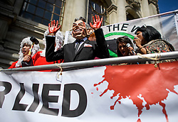 © Licensed to London News Pictures. 06/07/2016. London, UK. A man wearing a Tony Blair mask with his hands covered in fake blood, stands next to two people dressed as judges as protestors gather in Westminster, central London where the long-awaited Chilcot inquiry into the war in Iraq has been released. Photo credit: Ben Cawthra/LNP