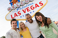 Two women and two men in front of Welcome to Las Vegas sign, group portrait
