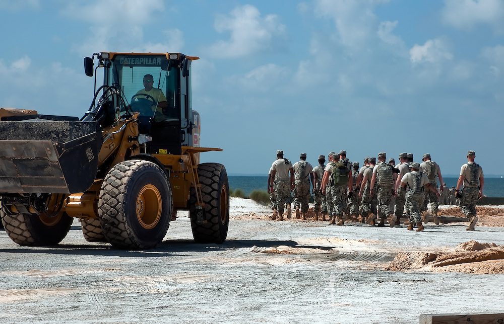 A MAECO equipment operator drives a front loader along the west end of Dauphin Island, Alabama, where efforts to protect the island from oil threatening as a result of the Deepwater Horizon rig explosion earlier in the month were heavily underway May 7, 2010. The National Guard spent most of the day installing nearly four miles of HESCO barriers and filling the felt-like boxes with sand chemically treated to transform the oil into a solid which can then be safely removed. (Photo by Carmen K. Sisson/Cloudybright)