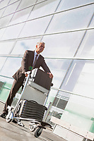 Portrait of mature businessman pushing luggage cart with his suitcase in airport