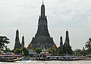 "Wat Arun (or Wat Arunratchawararam Ratchaworamahavihara, ""the Temple of the Dawn"") is a buddhist temple (wat) on the west bank of the Chao Phraya River in Bangkok, Thailand. The prang (Khmer-style tower) symbolizes Mount Meru of the Indian cosmology, and the side prangs honor the wind god Phra Phai.  They were started by Rama II in the early 1800s and completed by Rama III. The surrounding temple (originally known as Wat Makok, the Olive Temple) is much older, dating from the Ayuthaya period (1350 to 1767). The temple served as part of the palace of King Taksin, who reigned over Siam from 1768 to 1782 (just before the founding of Bangkok)."