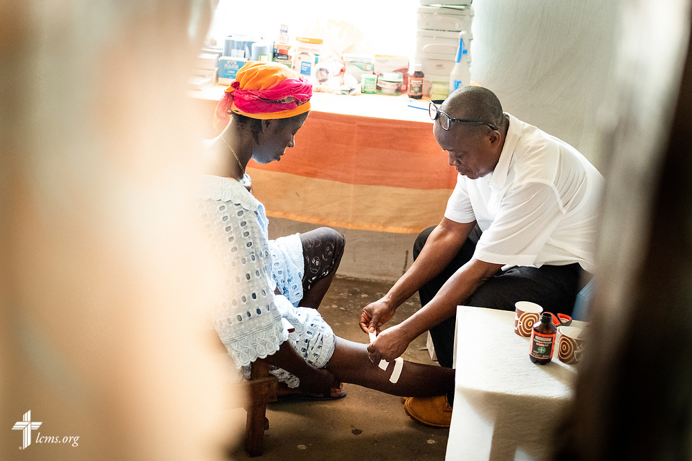 Michael Bio, a Sierra Leonean nurse studying to be a Community Health Officer, treats a patient during the second day of the LCMS Mercy Medical Team on Tuesday, May 8, 2018, in the Yardu village outside Koidu, Sierra Leone, West Africa. LCMS Communications/Erik M. Lunsford