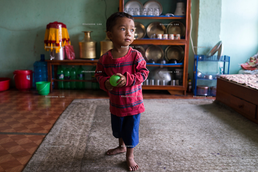 Sujal Tamang (2) stands as he plays with a ball in his aunt's rented apartment in Jorpati, Kathmandu, Nepal on 2 July 2015. Sujal was buried under the rubble of his collapsed house for 36 hours before rescuers found him injured with a broken leg next to his mother who was killed on the spot. Photo by Suzanne Lee for SOS Children's Villages