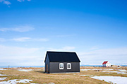 Traditional typical painted corrugated house black and grey, and melted snow on the ground near Reykjavik, Iceland