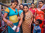 "22 OCTOBER 2015 - YANGON, MYANMAR: Hindus give out yogurt based drinks in the doorway of Sri Kali temple in Yangon on the last day of Navratri. Navratri, literally ""nine nights"" is a Hindu festival devoted to the Goddess Durga. Navratri festival combines ritualistic puja (prayer) and fasting. Navratri in India follows the lunar calendar and is celebrated in September/October as Sharad Navratri. It's widely celebrated in countries in Southeast Asia that have large Hindu communities, including Myanmar (Burma). Many of Myanmar's Hindus are descendants of Indian civil servants and laborers who came to Myanmar when it was the British colony of Burma.   PHOTO BY JACK KURTZ"