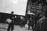 A homeless man walks past deigner brand Louis Vuitton store in Ginza, Tokyo, Japan.   MARCH 2004
