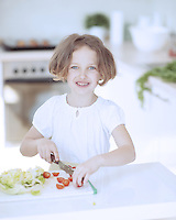 Young girl chopping tomatoes and making a salad in the kitchen