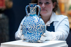 "© Licensed to London News Pictures. 20/04/2018. LONDON, UK. A technician presents ""A Unique blue and white pilgrim flask with animals"", Turkey, circa 1545-55, (Est. GBP60-80k) at a preview of works in Sotheby's 20th Century Middle East, Orientalist and Islamic upcoming art sales in New Bond Street.  The works will be sold at auction in the last week of April.    Photo credit: Stephen Chung/LNP"