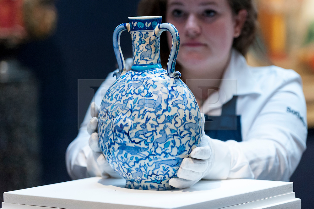 """© Licensed to London News Pictures. 20/04/2018. LONDON, UK. A technician presents """"A Unique blue and white pilgrim flask with animals"""", Turkey, circa 1545-55, (Est. GBP60-80k) at a preview of works in Sotheby's 20th Century Middle East, Orientalist and Islamic upcoming art sales in New Bond Street.  The works will be sold at auction in the last week of April.    Photo credit: Stephen Chung/LNP"""