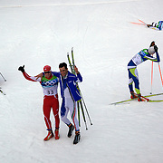 Winter Olympics, Vancouver, 2010.Dario Cologna, Switzerland, (33) winning Gold, is congratulated by Silver Medalist  Pietro Piller Cottrer, Italy,  as fellow competitors,  Lukas Bauer (34), Checkoslovakia, who won Bronze, Matti Heikkinen, Finland, (32) and Marcus Hellner, Sweden, (35) feel the pain at the finish after the Men's 15km Cross Country Skiing event at The Whistler Olympic Park, Whistler, during the Vancouver Winter Olympics. 14th February 2010. Photo Tim Clayton