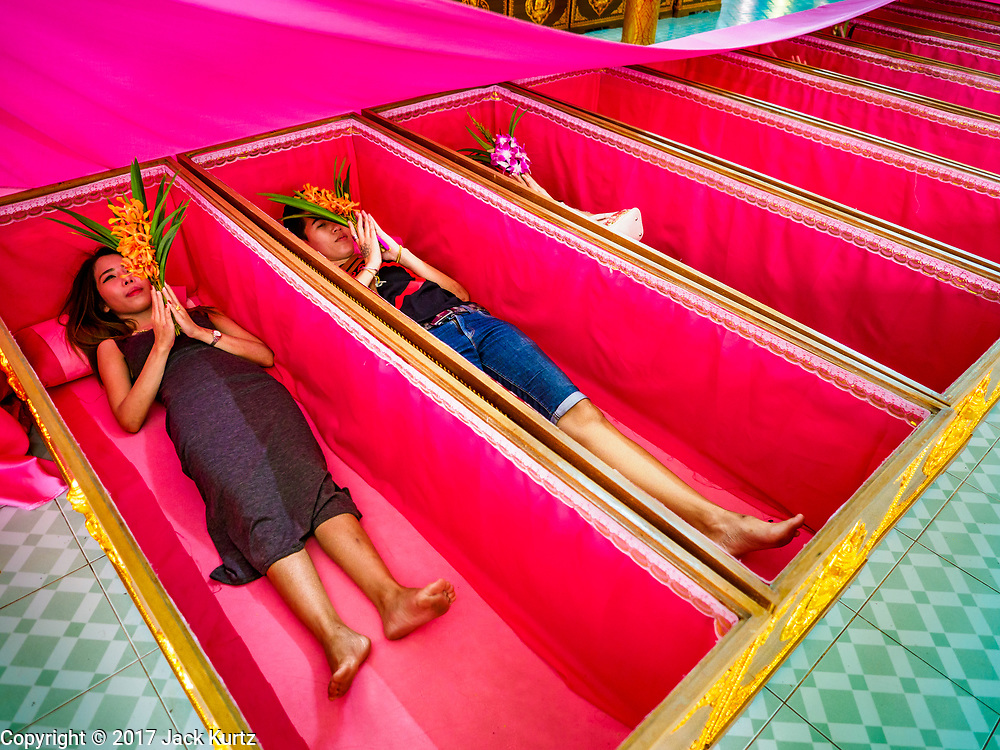 """24 JUNE 2017 - BANG KRUAI, NONTHABURI: People lay in their coffins during a """"resurrection"""" or rebirthing ceremony at Wat Ta Kien (also spelled Wat Tahkian), a Buddhist temple in the suburbs of Bangkok. People go to the temple to participate in a """"Resurrection Ceremony."""" Thai Buddhists believe that connecting people by strings around their heads, which are connected to a web of strings suspended from the ceiling, amplifies the power of the prayer. Groups of people meet and pray with the temple's Buddhist monks. Then they lie in coffins, the monks pull a pink sheet over them, symbolizing their ritualistic death. The sheet is then pulled back, and people sit up in the coffin, symbolizing their ritualist rebirth. The ceremony is supposed to expunge bad karma and bad luck from a person's life and also get people used to the idea of the inevitability of death. Most times, one person lays in one coffin, but there is family sized coffin that can accommodate up to six people. The temple has been doing the resurrection ceremonies for about nine years.     PHOTO BY JACK KURTZ"""