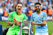 Ederson Moraes (31) of Manchester City holds the FA Cup with Riyad Mahrez (26) of Manchester City during the celebrations at full time during the The FA Cup Final match between Manchester City and Watford at Wembley Stadium, London, England on 18 May 2019.