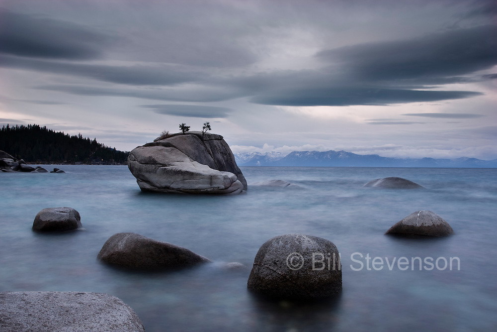 A photo of Bonsai Rock on the Nevada shore of Lake Tahoe. Normally photographers go in search of the most spectacular morning and evening light but the day this was created was overcast but I just like going out to shoot. The way the shapes in the clouds mirror the  arrangement of the rocks is what makes this shot for me. The shutter was left open for an extended period in order to smooth\blur the water.