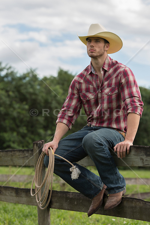 cowboy sitting on a wooden fence on a ranch