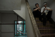 For a story by Dan Levin slug Hong Kong.February 22 2013, Kowloon, Hong Kong.In a staircase of the Chungking Mansions, two cooks from a nearby fast food restaurant are taking a cigarette break..Credit: Gilles Sabrie for The New York Times..