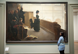 Woman looking at painting The Organ Rehearsal by Henry Lerolle at Metropolitan Museum of Art in Manhattan , New York City, USA