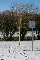 Snow covered field in suburban in Dublin Ireland, sign has notice about keeping dogs on a lead