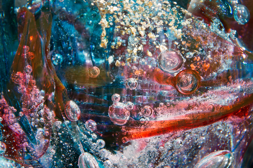 Bubbles and gold flakes swirling through blue and red glass, a fine art abstract done in micro photography.