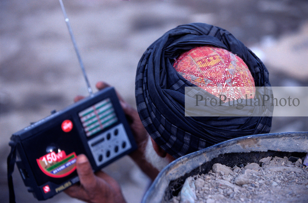 Kabul, 24 July 2005. A man wearing the traditional turban is listening to the radio