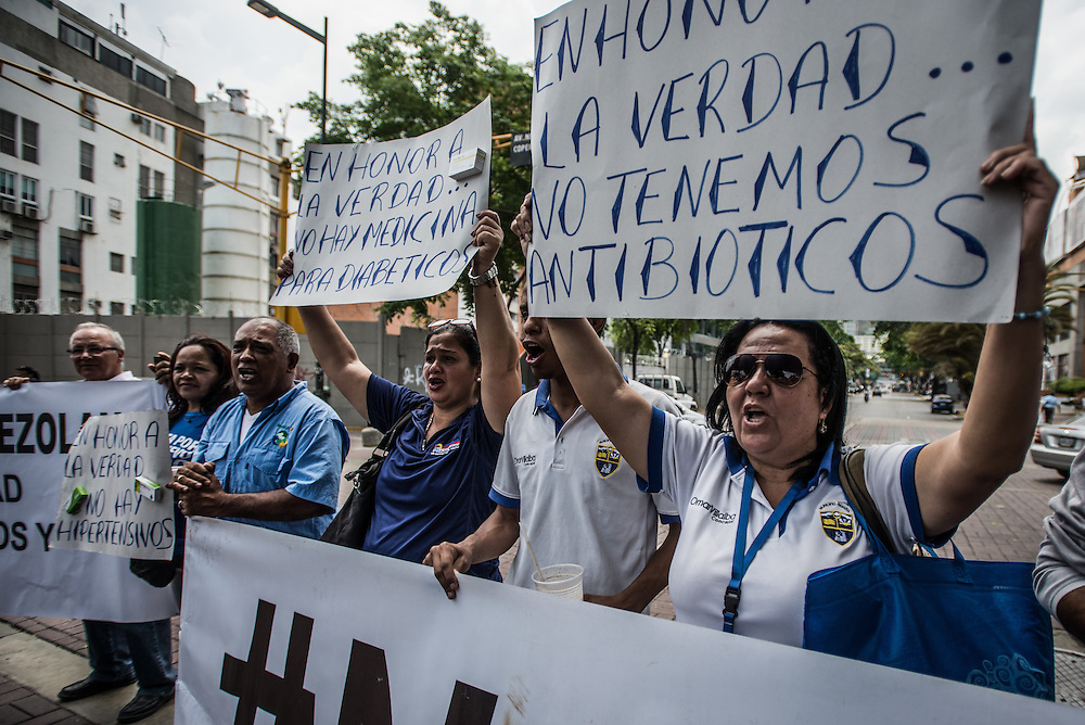 "CARACAS, VENEZUELA - APRIL 13, 2016:  Doctors, patients and their families block traffic during a protest against the hospital crisis.  These women held signs that say in Spanish, ""In honor of the truth, we have no antibiotics"" and ""In honor of the truth, there is no medicine for diabetics"". Despite having the largest oil reserves in the world, falling oil prices and wide-spread government corruption have pushed Venezuela into an economic crisis, with the highest inflation in the world and chronic shortages of food and medical supplies.  PHOTO: Meridith Kohut for The New York Times"