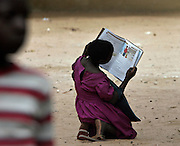 A young girl reads a book on HIV Aids outside her Primary School after class was dismissed for the day in Mausse, Mozambique. (2005)