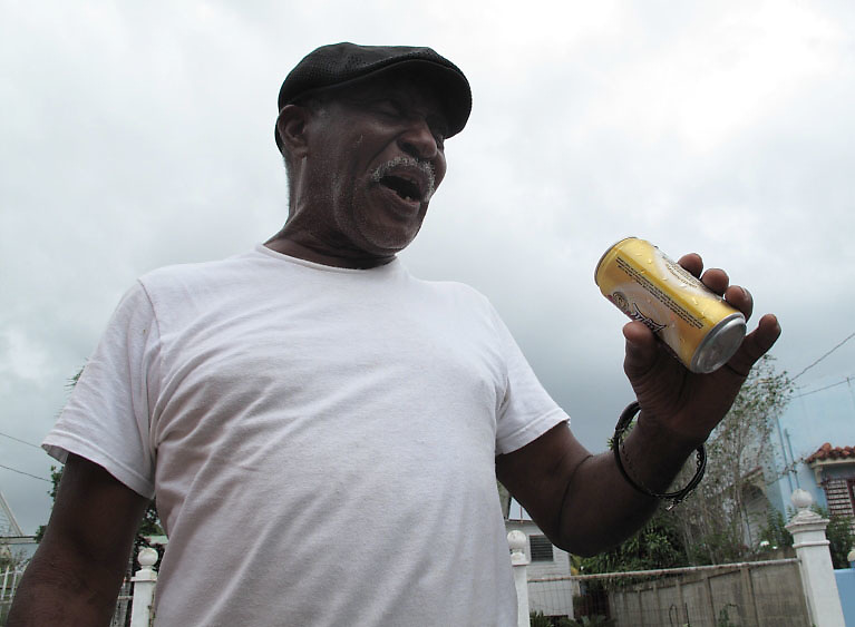 2/15/09---Older man singing to tunes played on sound system using a Medalla ber can as microphone  in the carnival in the southern town of Arroyo in Puerto Rico..Photo by Angel Valentin, copyright 2009. NO MODEL RELEASE.