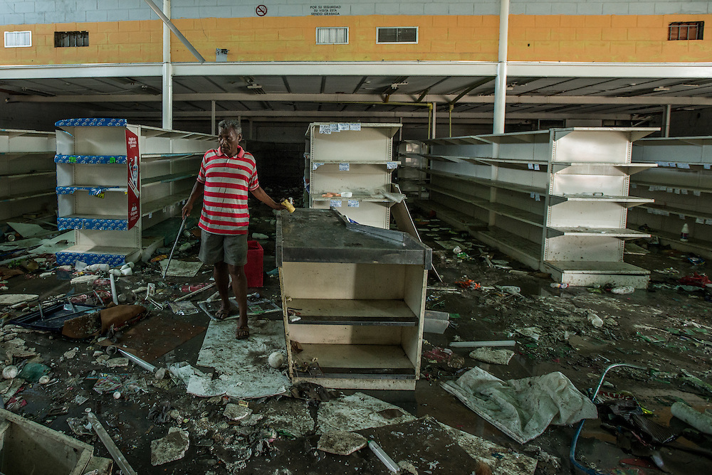 CUMANÁ, VENEZUELA - JUNE 16, 2016: A man searches for anyting he can salvage from a grocery store that was destroyed last Tuesday by hundreds of looters in Cumaná, Venezuela. They made it through the doors before the owners could close them, forced a large metal gate open so those outside could pour inside. They took water, flour, corn meal, salt, sugar, potatoes, cereal—leaving behind only a broken freezers and overturned shelves. And they proved that even in country with the richest oil reserves in the world, it was possible for people to riot because there was no food. Venezuela is convulsing from a raft of violence triggered by hunger. It is latest chapter of an economic collapse which has left the country neither able to produce its food nor import it from abroad, leaving a nation searching for how to feed itself. In the past 11 days, scores of businesses, mostly stores, have been looted or destroyed and five people have died in the confrontations. With delivery trucks under constant attack, the nation's food is now transported under armed guard. Entire cities have been militarized under an emergency decree from President Nicolás Maduro; bakeries are now watched over by the National Guard.  PHOTO: Meridith Kohut