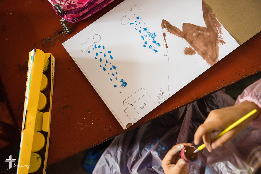 A young student paints artwork at the Noe (Spanish for Noah) school on Tuesday, April 7, 2015, depicting recent heavy rains and landslides that caused devastation to regions around Lima, Peru. LCMS Communications/Erik M. Lunsford