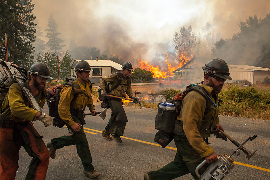 Firefighters flee as the Twisp River fire advances unexpectedly near Twisp, Washington August 20, 2015.  Three firefighters in Washington state were killed and four injured while battling a wildfire threatening the town of Twisp, officials said on Wednesday, as more than a dozen major blazes burned in parched Western U.S. states. REUTERS/David Ryder