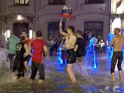 Carnival atmosphere as Russian fans in a fountain near Red Square, Moscow celebrate their victory over Spain in the last 16 at the 2018 FIFA World Cup in, Russia.
