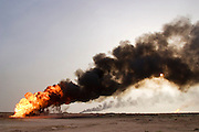One of the oil wells set ablaze by retreating Iraqi troops in the southern Iraq Rumaila oil field (and one in the distance). The wells were set on fire with explosives placed by retreating Iraqi troops when the US and UK invasion began in March of 2003. Seven or 8 wells were set ablaze but at least one other was detonated but did not ignite. The Rumaila field is one of Iraq's biggest with five billion barrels in reserve. Rumaila is also spelled Rumeilah.