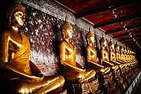 Buddha statues line the walls at Wat Suthat in Bangkok, Thailand.