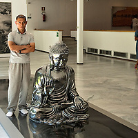 MILAN, ITALY - JULY 06:   Chinese artist Zhang Huan poses next to ''Buddha of Steel Life' at the opening of the Exhibition 'Zhang Huan: Ashman' at the Padiglione Arte Contemporanea of Milan on July 6, 2010 in Milan, Italy. Zhang Huan: Ashman is  an exhibition of 42 of Huan's works, coming from international collections and dating from the early nineties to the most recent realized with ash....***Agreed Fee's Apply To All Image Use***.Marco Secchi /Xianpix. tel +44 (0) 207 1939846. e-mail ms@msecchi.com .www.marcosecchi.com