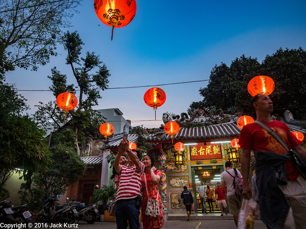 "08 FEBRUARY 2016 - BANGKOK, THAILAND: People take ""selfies"" in front of a small shrine in Bangkok's Chinatown district during the celebration of the Lunar New Year. Chinese New Year is also called Lunar New Year or Tet (in Vietnamese communities). This year is the ""Year of the Monkey."" Thailand has the largest overseas Chinese population in the world; about 14 percent of Thais are of Chinese ancestry and some Chinese holidays, especially Chinese New Year, are widely celebrated in Thailand.       PHOTO BY JACK KURTZ"