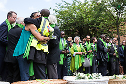 London, UK. 14th June, 2018. Family members embrace whilst faith leaders and politicians hold flowers outside St Helen's Church to mark the first anniversary of the Grenfell Tower Fire.
