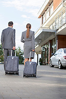 Back view of businesspeople walking with luggage outside hotel