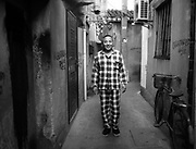 A man poses in a narrow alley in his pajamas, popularly worn as leisure wear in Shanghai.