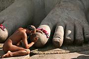 A Digambar Jaina devotee prays on the feet of the statue of Gomateswara Bahubali in Sravanbelagola in the state of Karnataka in India.