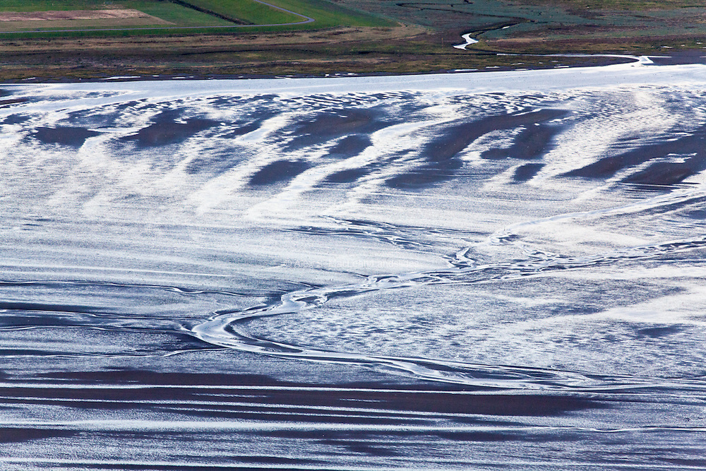 Reflected light reveals the stream and flow of water on the flat tidal beds along the south side of Wangerooge.