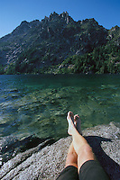 A mans legs seen from thigh down laying on a rock at the edge of a mountain lake<br />