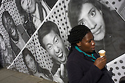 A woman eats an ice cream cone while passing a construction hoarding featuring many faces and expressions.