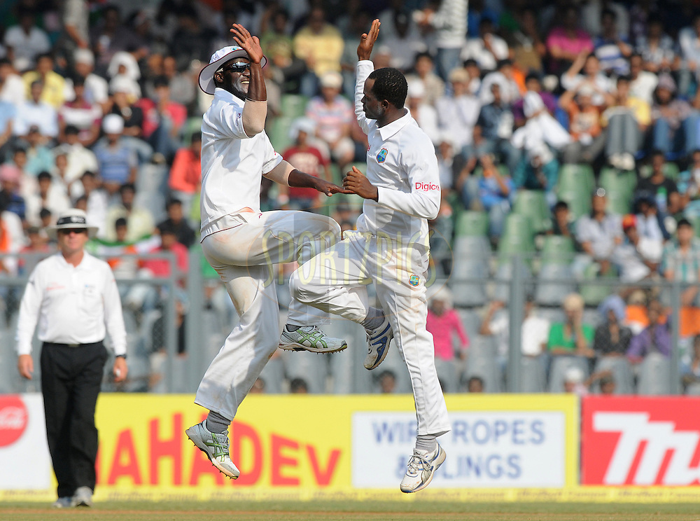 Darren Sammy captain of West Indies and Marlon Samuels of West Indies celebrate the wicket of Rahul Dravid of India during the 3rd day of the 3rd test match between India and The West Indies held at Wankhede Stadium in Mumbai, India on the 24th November 2011..Photo by Pal Pillai/BCCI/SPORTZPICS
