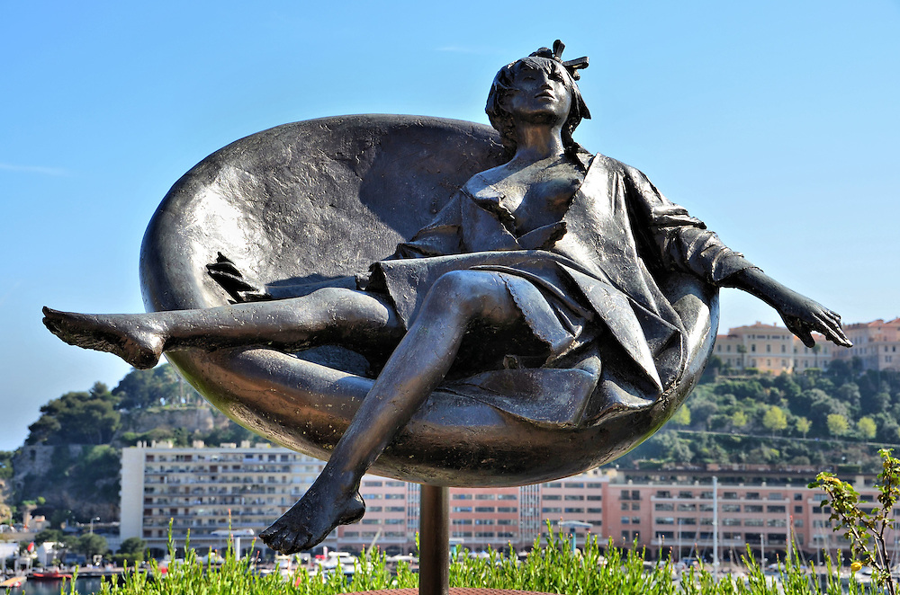 Tebe in Costume Sculpture in Monte Carlo, Monaco <br /> This bronze sculpture by Giacomo Manzu of a distinguished woman reclined in an oval chair is called &ldquo;Tebe in Costume.&rdquo;  It was placed along Avenue d&rsquo;Ostende in 1982 near the Princess Grace Theater.  In the background is Port Hercules, the coast of the La Condamine ward and, under her left hand, the Palais Princier on Le Rocher.
