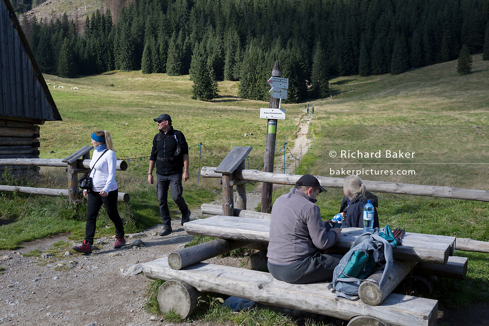 Walkers rest and make their way down a mountain footpath in  Polana Chocholowska, a hiking route in the Polish Tatra mountains, on 17th September 2019, near Zakopane, Malopolska, Poland.