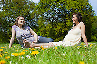Pregnant women sitting on grass