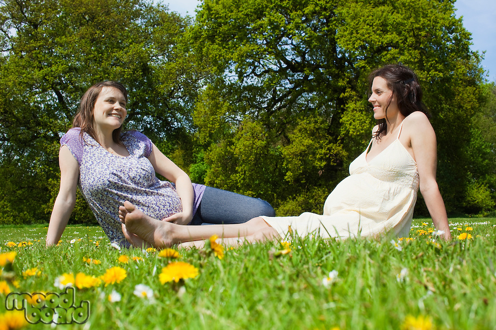 Pregnant women sitting on grass