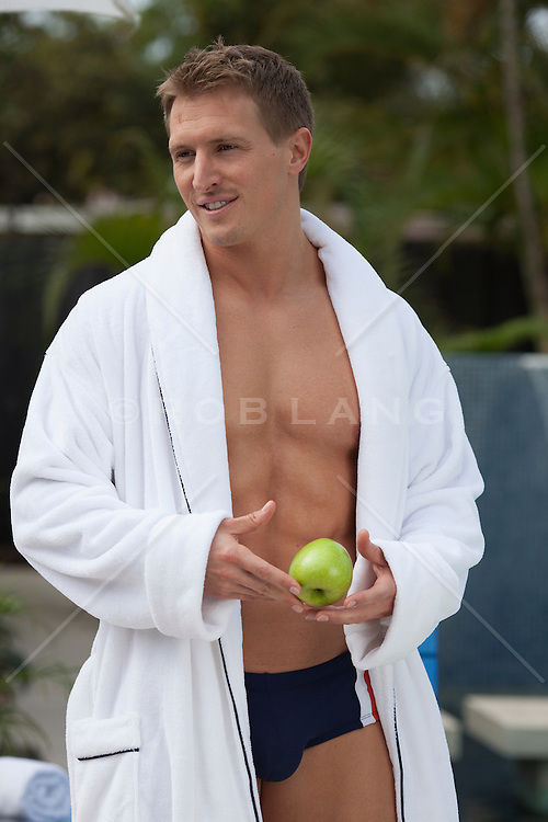 All American man in a white robe at home by a swimming pool in Florida